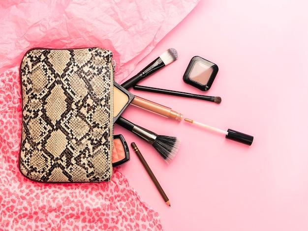 ヘビのデザインと装飾的な様々な化粧品アクセサリーの美しい化粧バッグのフラットレイアウト Premium写真