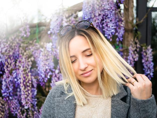 Белокурая девушка с круглыми стеклами на предпосылке весенней глицинии. Premium Фотографии