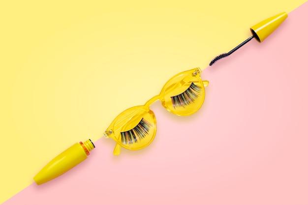 偽まつげ付きのピンクと黄色のサングラスに開いたブラシと黄色のチューブのマスカラ。 Premium写真