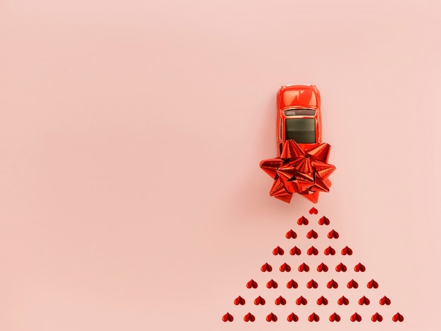 バレンタインの日にハートの紙吹雪とピンクの背景に赤の弓と赤いレトロなおもちゃの赤い車 Premium写真
