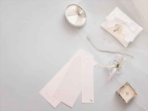 最小限のフラットは明るいベールの背景に結婚式のアクセサリーと一緒に置きます。 Premium写真