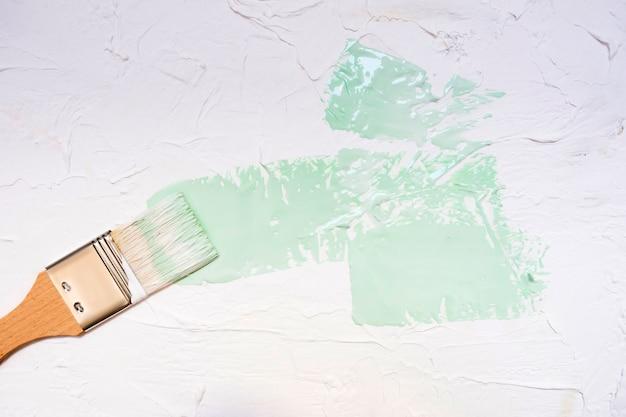 Кисть с цветной краской на белом фоне стены Premium Фотографии
