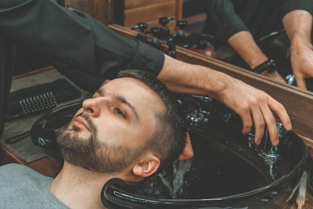 Парикмахерская, мужчина моет волосы. парикмахерская моет своего клиента. вымойте волосы и бороду после стрижки. личная гигиена Premium Фотографии