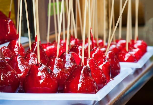 キャラメル化された赤いリンゴとナシ、みかん Premium写真