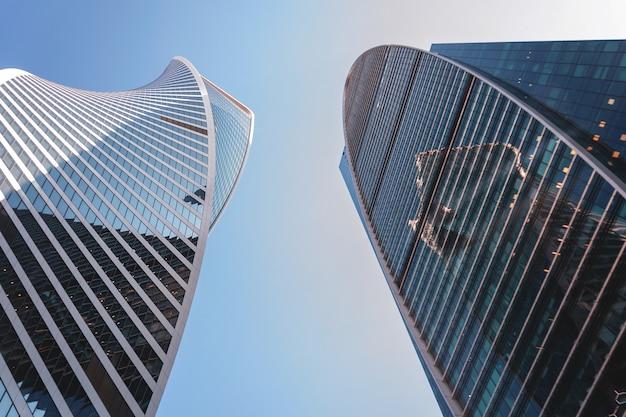 空を背景にガラスの超高層ビル。銀行、オフィス、本社ビル。 Premium写真