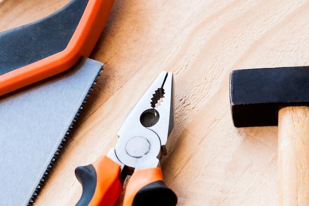 ハンマー、釘、ペンチは木製の背景にあります。 Premium写真
