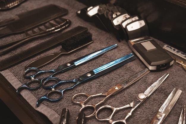 Парикмахерская инструмент в парикмахерской. парикмахерский инструмент. ножницы, расчески, бритвы, машинки для стрижки. инструмент для мастера. организация рабочего места. выборочный фокус. Premium Фотографии