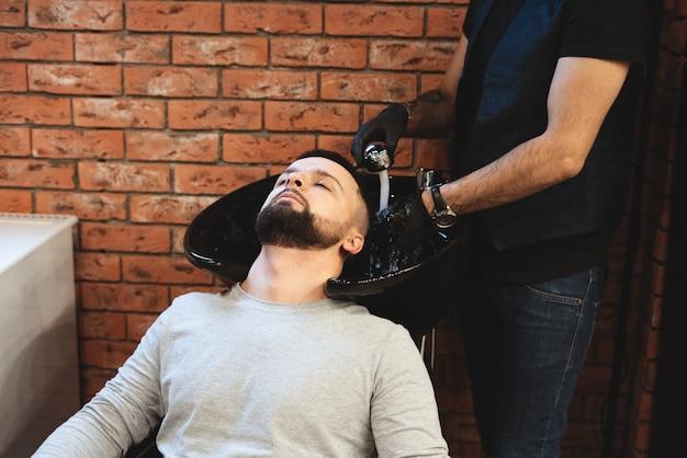 理髪店では、男性が髪を洗われます。 Premium写真