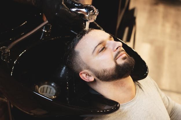 В парикмахерской мужчина моет волосы. парикмахер моет своего клиента. вымойте волосы и бороды после стрижки. личная гигиена. Premium Фотографии