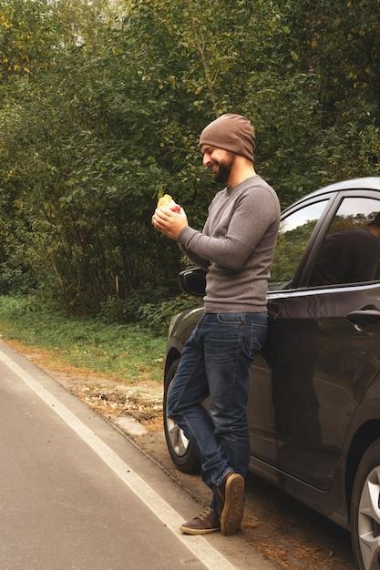 Молодой парень ест гамбургер возле автомобиля на пустой дороге. еда в поездке. еда на ходу. осеннее путешествие. быстрое питание. Premium Фотографии