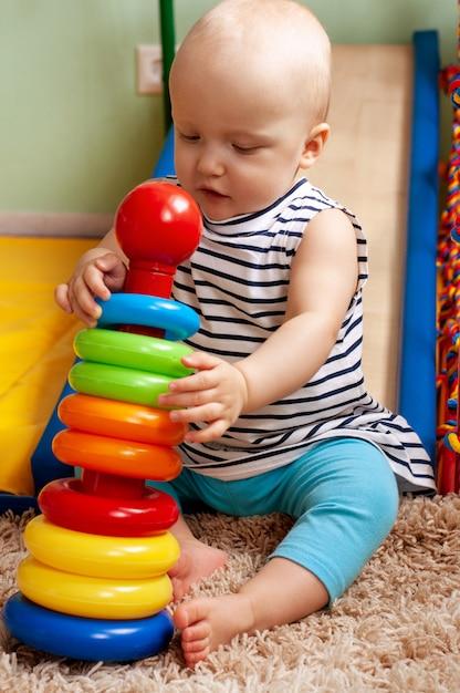 Развивающие логические игрушки для детей. ребенок собирает цветную пирамиду. монтессори-игры для развития ребенка. ранняя разработка Premium Фотографии