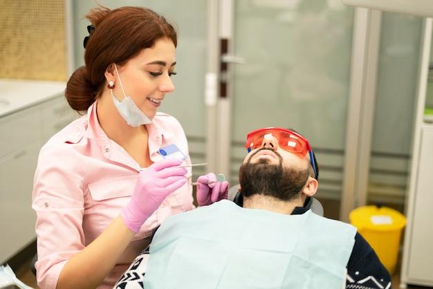歯科医の若い女性は、患者を男を扱います。医師は使い捨て手袋、マスク、帽子を使用します。歯科医は患者の口で働き、プロのツールを使用します Premium写真