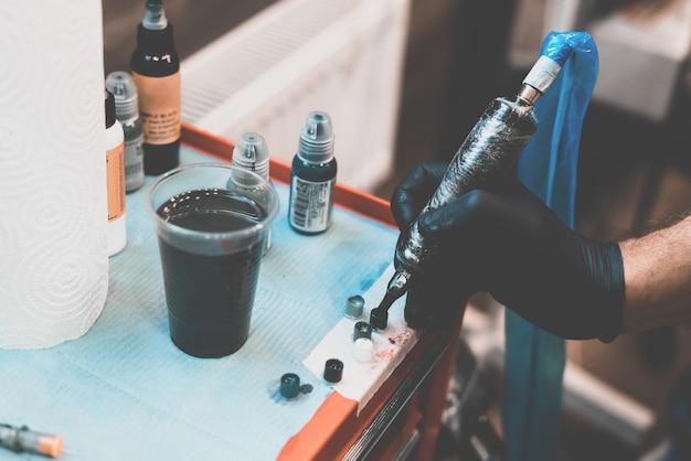 Тату салон. тату-машина и подготовленные краски для татуировки на столе. процесс отверждения краски. крупный план, тонировка, татуировщик. Premium Фотографии