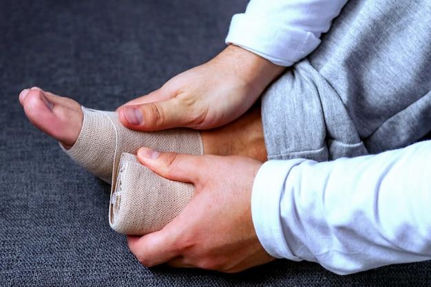 男がスポーツ用包帯で足を包帯します。スポーツにおける怪我と緊張 Premium写真