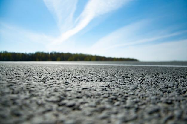 絵のような風景と道路上の日の出。マーキングのあるアスファルト道路。ぼかし付き。 Premium写真