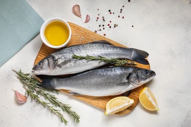 Свежая рыба сибаса и ингредиенты для приготовления, лимон и розмарин. белый фон вид сверху. Premium Фотографии