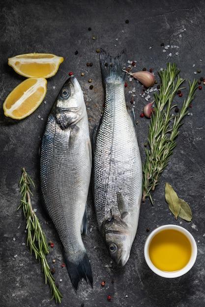 Свежая рыба сибас и ингредиенты для приготовления, лимон и розмарин. темный фон вид сверху. Premium Фотографии