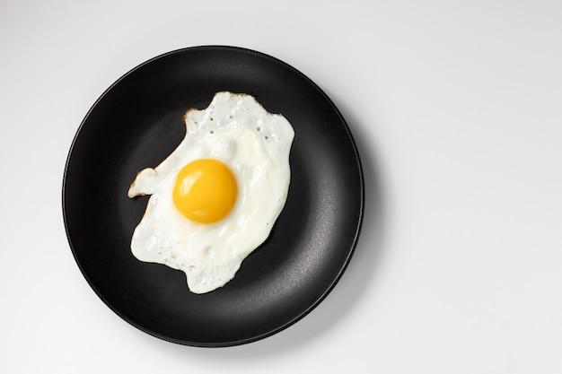 黒い皿に目玉焼き。白い背景に分離します。 Premium写真