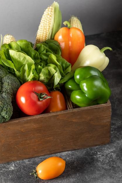 Свежие овощи в деревянной коробке на темном деревянном фоне Premium Фотографии