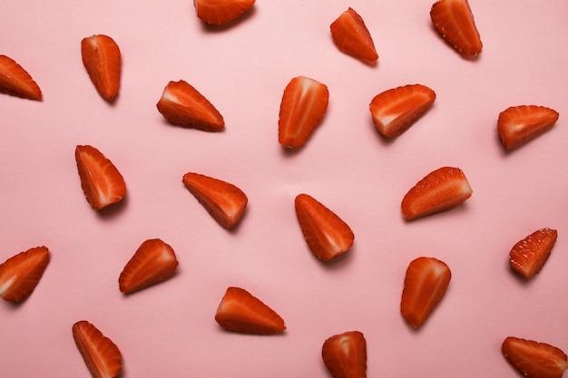 パステルピンクの表面にイチゴのパターン。夏のコンセプトです。フラットレイアウト、平面図、正方形 Premium写真