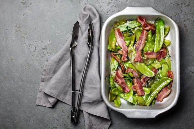 金属の鍋でベーコンと揚げエンドウ豆の鞘 Premium写真
