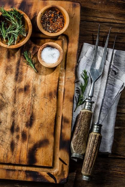 料理の背景のコンセプトです。カトラリーとビンテージのまな板。上面図 Premium写真