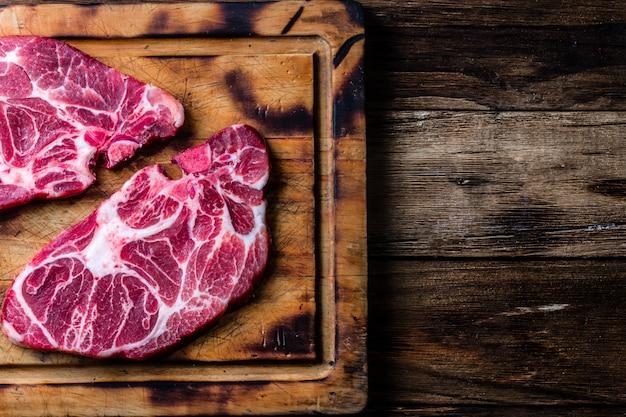 木製のまな板に生の大理石のビーフステーキ Premium写真