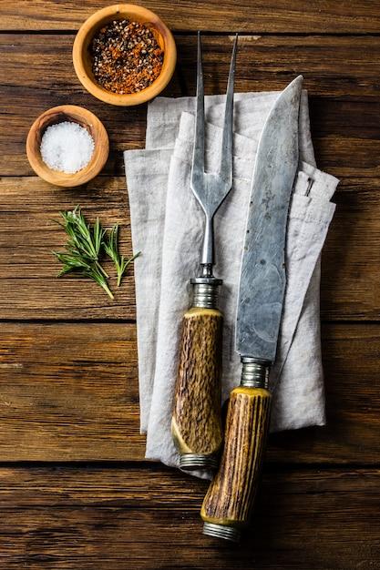 料理の背景のコンセプトです。ビンテージカトラリー、木製の背景にスパイス。 Premium写真