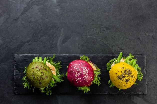 Цветные зеленые, желтые и фиолетовые гамбургеры на грифельную доску. вид сверху Premium Фотографии