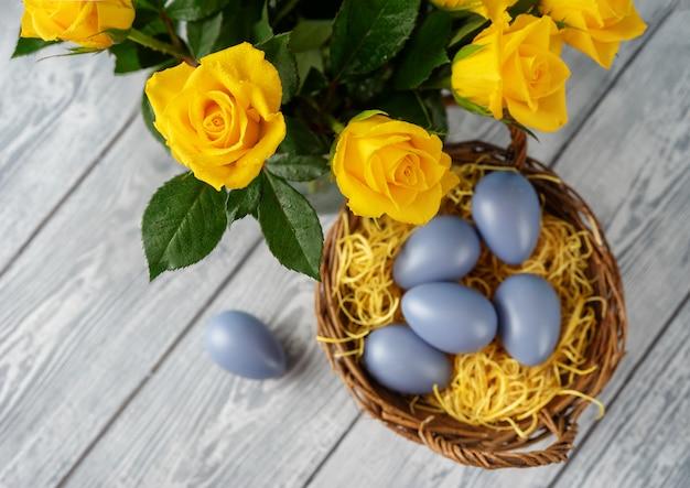 Пасхальные яйца в корзине и желтые розы, вид сверху Premium Фотографии