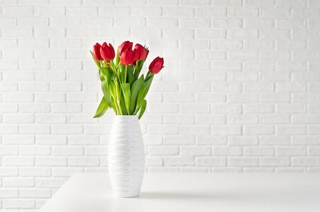 白いレンガの背景に白い花瓶の赤いチューリップ Premium写真