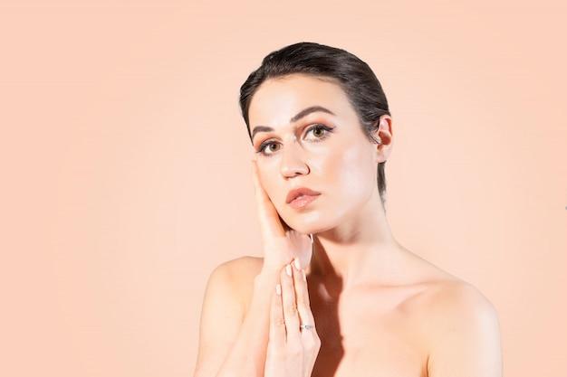 彼女に触れる明確な肌を持つ若い女性は彼女の顔を手します。 Premium写真