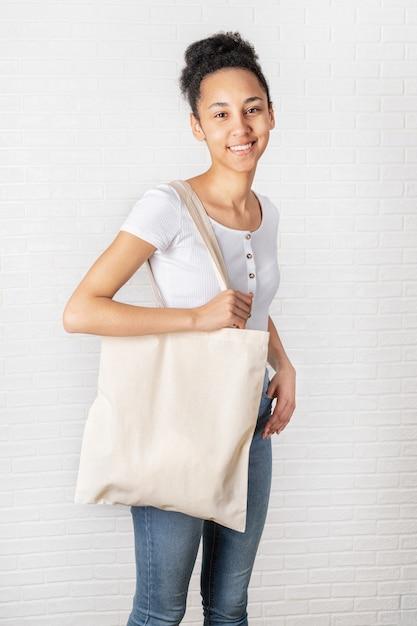 白いエコバッグを保持している若いアフリカ人女性 Premium写真