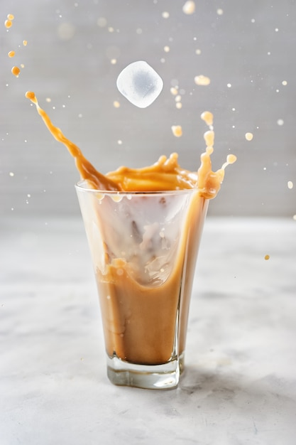 灰色の背景上のガラスの上のスプラッシュとアイスコーヒー Premium写真