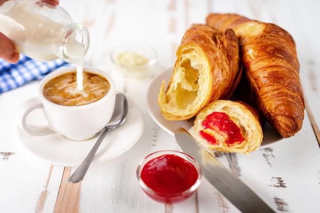 一杯のコーヒーとクロワッサンを朝食します。 Premium写真