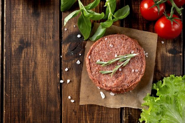 Вид сверху сырой веганский пирожок на темной деревянной поверхности Premium Фотографии