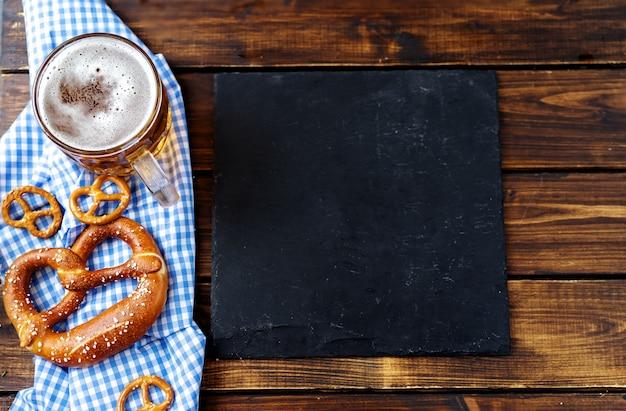 ビールジョッキ、プレッツェル、木製のテーブルのソーセージ。上面図 Premium写真