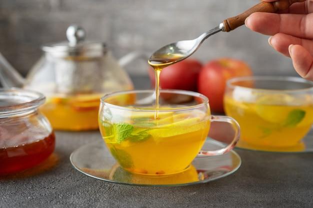 フルーツティーのガラスカップに蜂蜜を注ぐ Premium写真