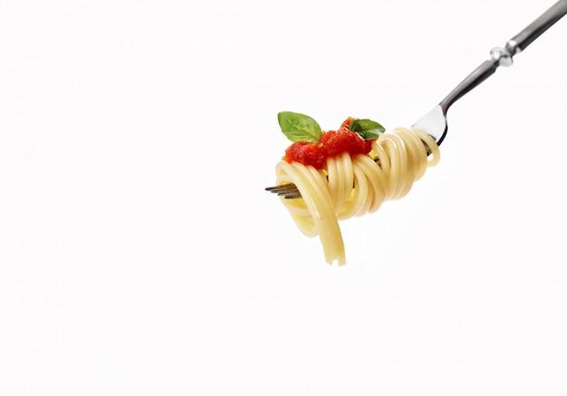 Вилка со спагетти, помидорами, лососем и базиликом Premium Фотографии