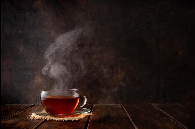 暗闇の中で蒸気と熱いお茶のカップ Premium写真