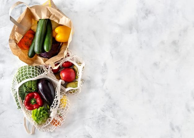白い背景の上のネットと紙袋の野菜と果物 Premium写真