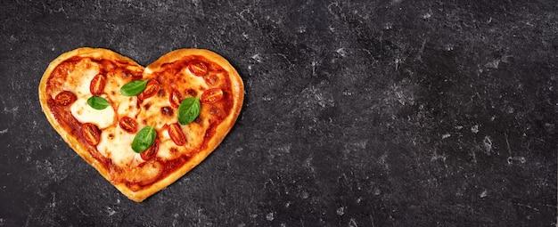 Вкусная итальянская пицца на черном в форме сердца Premium Фотографии