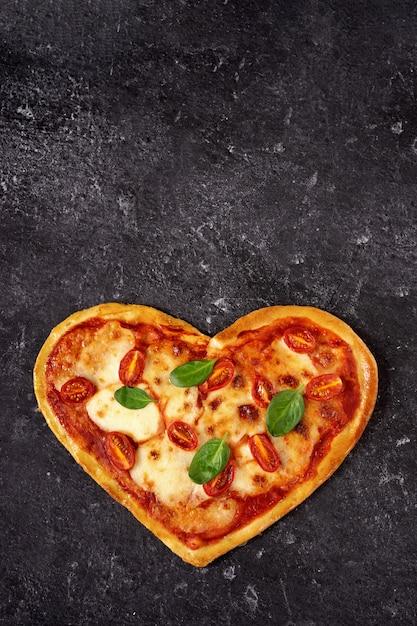 Домашняя вегетарианская пицца в форме сердца на черном Premium Фотографии