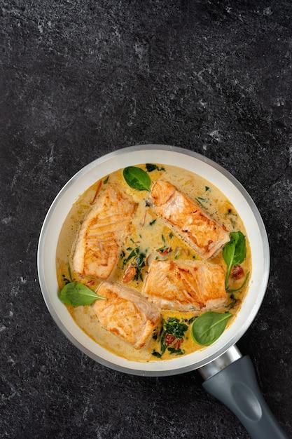 Крупным планом стейки лосося в сливочном соусе на черном Premium Фотографии