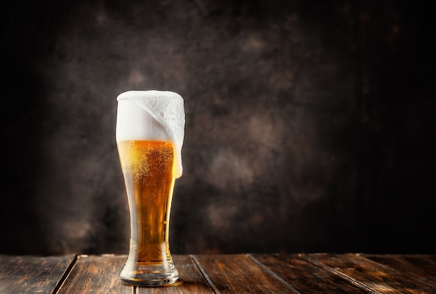 暗い背景に新鮮で冷たいビールのグラス Premium写真