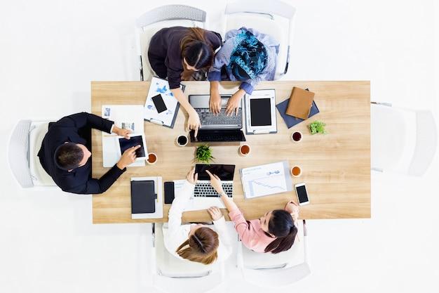 ビジネスチームの同僚は現代の事務室で彼のラップトップ電話に取り組んで仕事 Premium写真