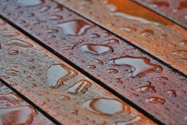 木の床の表面に水滴します。雨の後雨滴と木の上の水の滴。 Premium写真