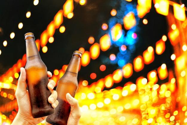 ビールのボトルを保持していると、素晴らしく眼鏡に収穫時間を一緒に楽しんで幸せ。 Premium写真