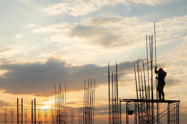 安全上の労働者のシルエットは工事現場で高い地面と鋼鉄棒から立っています。 Premium写真