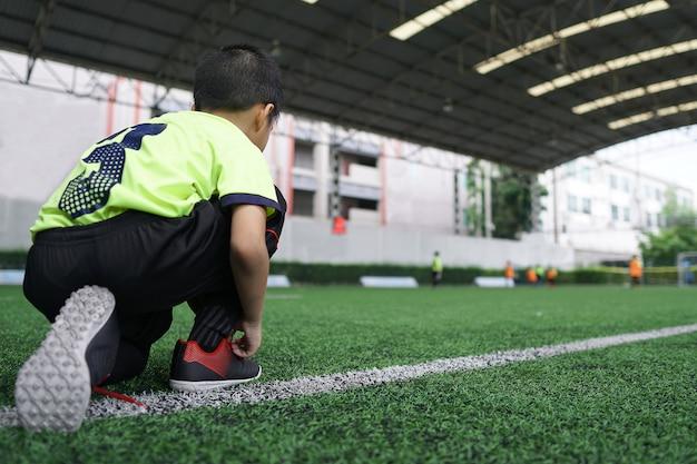 アジアの少年がサッカー芝スポーツ分野で準備します。 Premium写真